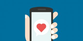 Graphic of hand holding mobile phone with heart on the screen.
