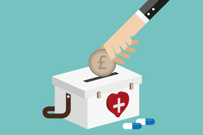 Graphic illustration of hand putting pound coin into moneybox with heart and cross on outside with two pills lying next to it to show NHS financial management and sustainability