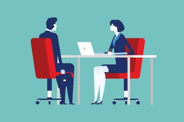 Woman interviewing man at a desk demonstrating a successful key account manager