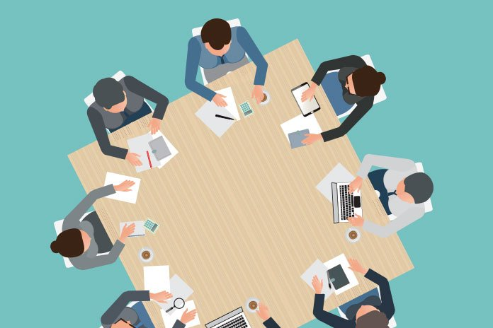 Cartoon image of business people sitting round a table to show implementing agile in pharma