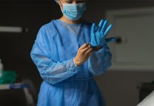 Image of a surgeon putting on PPE to how NHS roadmap to safely bring back routine operations during COVID-19