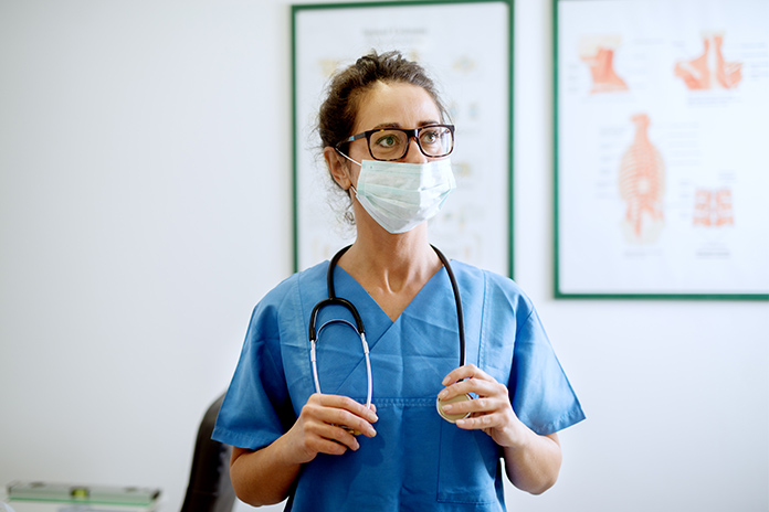 Image of a healthcare professional in a face mask to show First UK participant enters the largest COVID-19 interventional trial investigating hydroxychloroquine