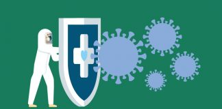 Image of a person in full PPE holding a shield with a health cross on it up to the coronavirus to show New consortium to monitor safety and effectiveness of COVID-19 vaccines