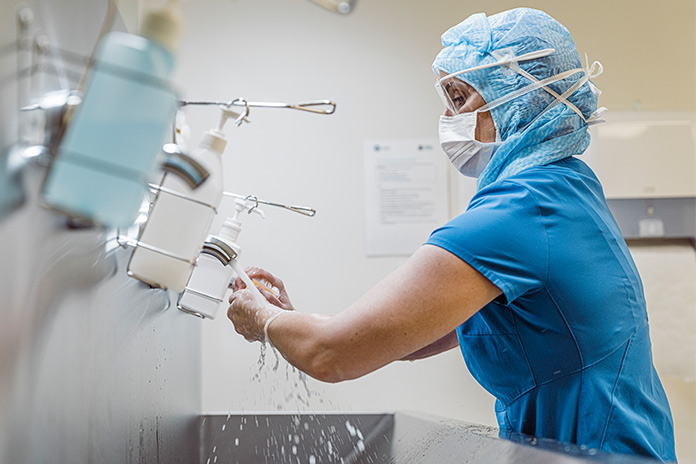 Image of a healthcare professional in PPE washing their hands to show First human trials of Imperial College COVID-19 vaccine to start