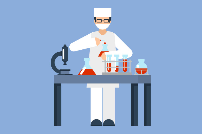 Image of a lab technician at a table with a microscope and medical glassware to show New study into link between IBD and risk of colorectal cancers at molecular level